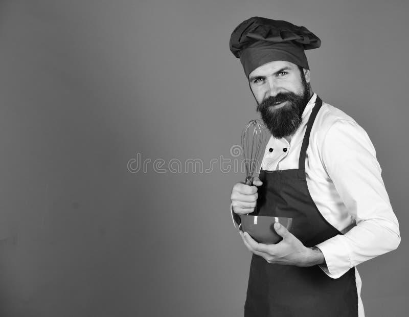 Bageri och matlagning Kock med den röda plattan och piskaredskapet arkivfoton
