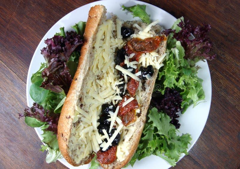 Bagette com Mozzarella, azeitonas pretas e o tomate Sun-Dried imagens de stock