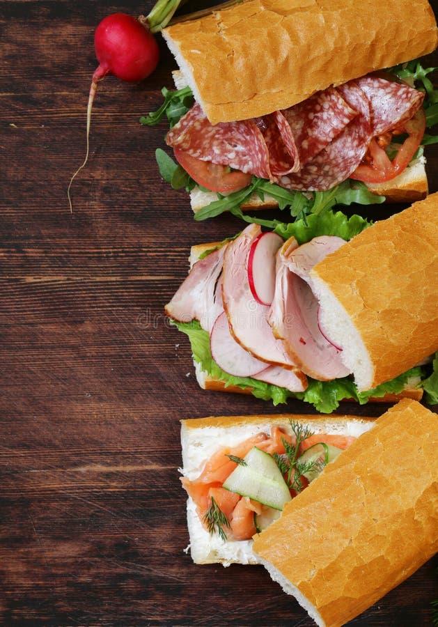 Bagettsmörgås med laxen och skinka royaltyfria foton