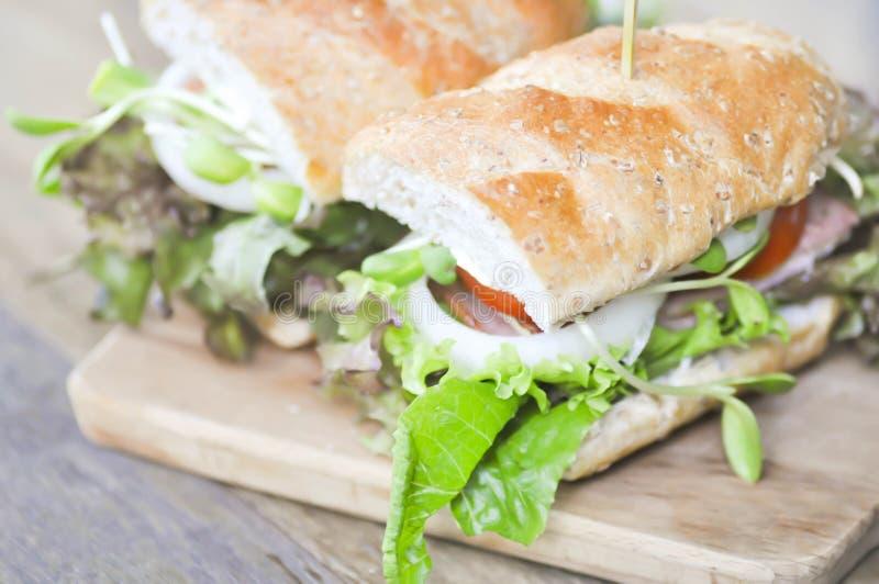 Bagettsmörgås med skinka, tomaten och grönsallat fotografering för bildbyråer