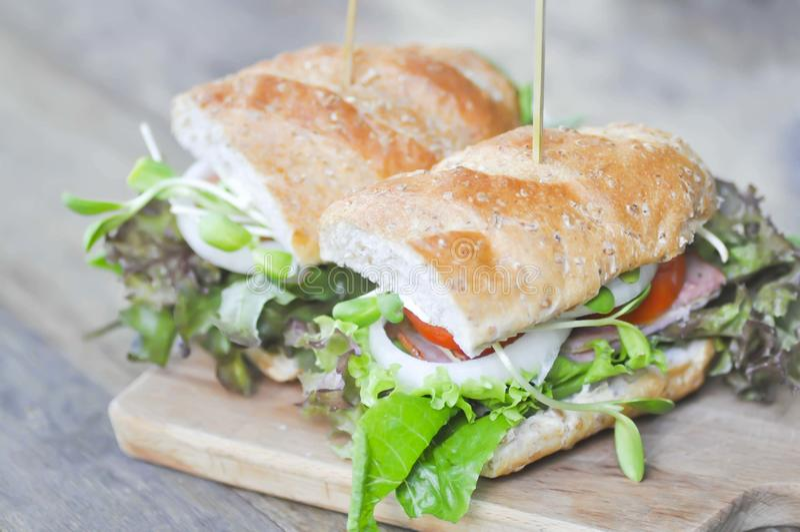 Bagettsmörgås med skinka, tomaten och grönsallat arkivbilder