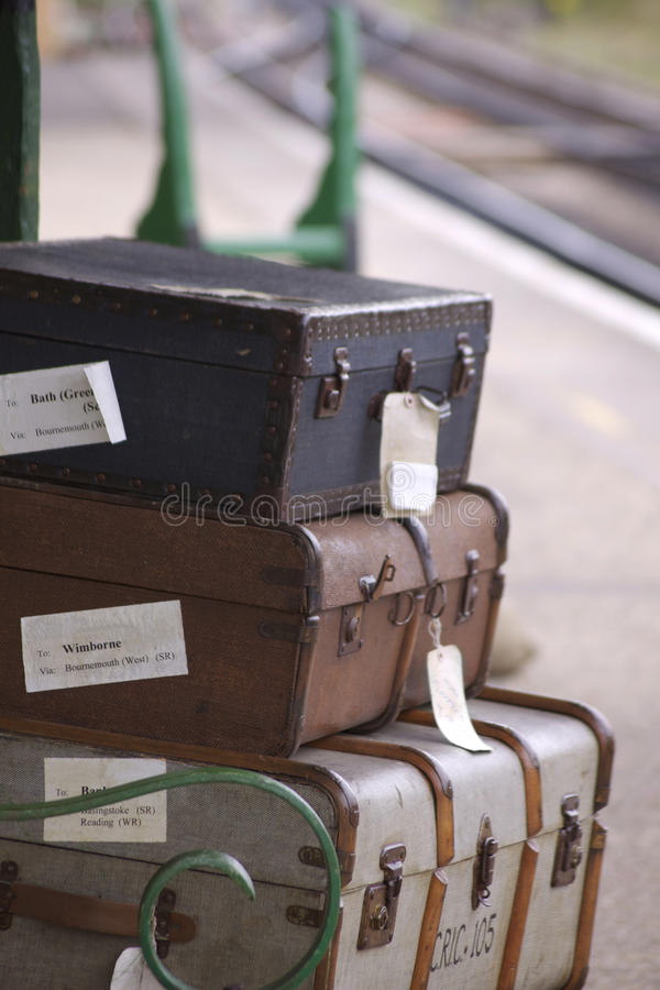 Baggage. A set of period luggage consisting of old leather cases, set on a trolly on the platform of a retro railway station. Location at Harmans Cross station stock image