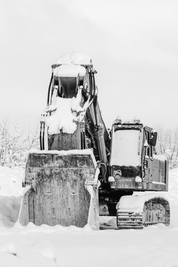 Bagger, der draußen im Schnee im Winter, Abschluss oben steht lizenzfreies stockfoto