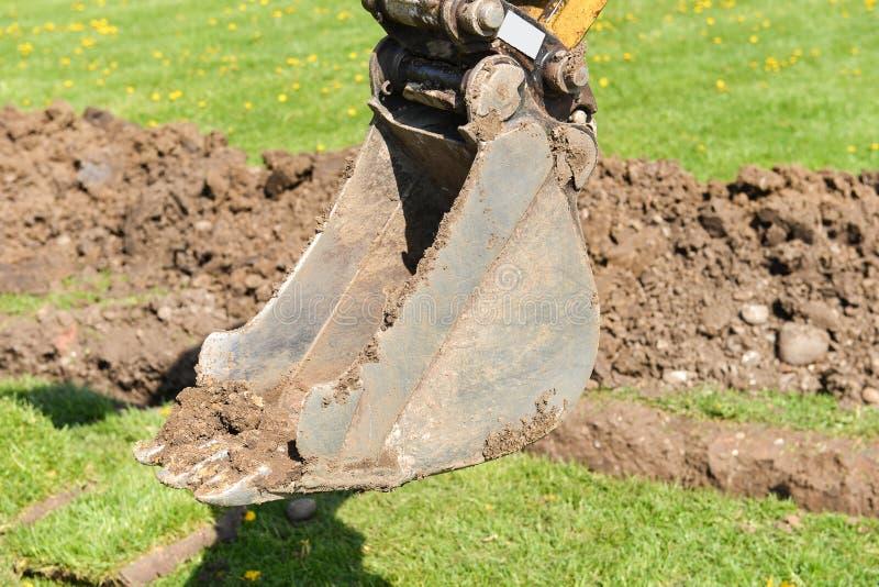 Baggerarm, der tief, Arbeiten über eine Baustelle gräbt stockfotografie