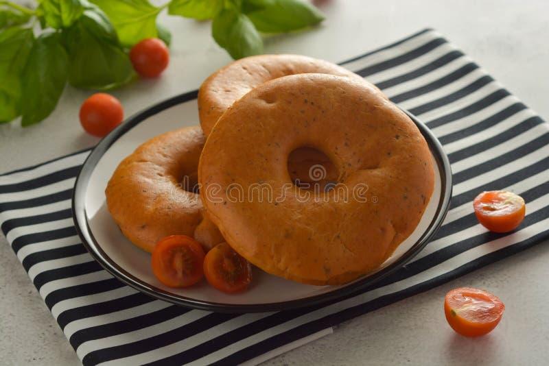 Baglar som isoleras på ljust bräde med basilika och körsbärsröda tomater för frukostbakelse arkivbilder
