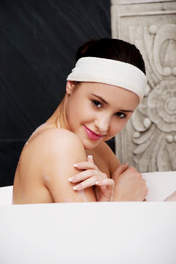 Bagnando donna che si rilassa nel bagno fotografia stock