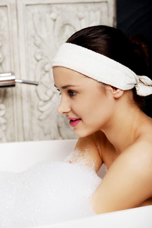 Bagnando donna che si rilassa nel bagno fotografia stock libera da diritti