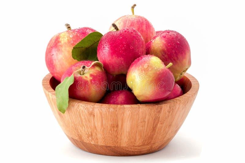 Bagni le mele chiazzate organiche in una ciotola di bambù isolata su fondo bianco fotografia stock