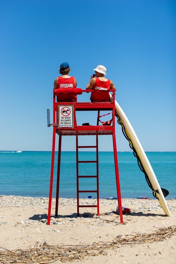 Bagnini osservando spiaggia dalla torre immagine stock