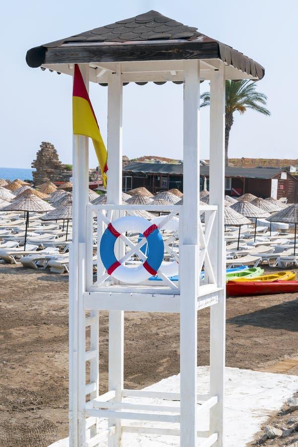 Bagnino di legno bianco con il salvagente e bandiera sulla spiaggia sabbiosa fotografia stock libera da diritti