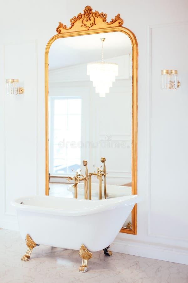 Bagno bianco d'annata di colore vicino allo specchio con una struttura dorata Art deco Interiore di lusso fotografie stock libere da diritti