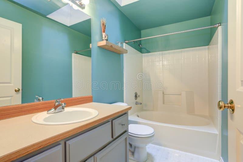 Bagno blu verde intenso con la vasca bianca e doccia combinata fotografie stock libere da diritti