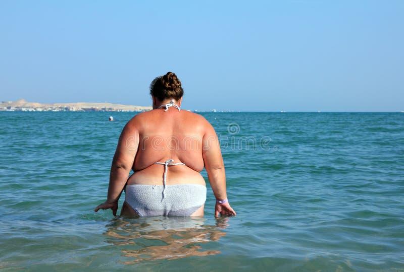 Bagno di peso eccessivo della donna in mare fotografia stock libera da diritti