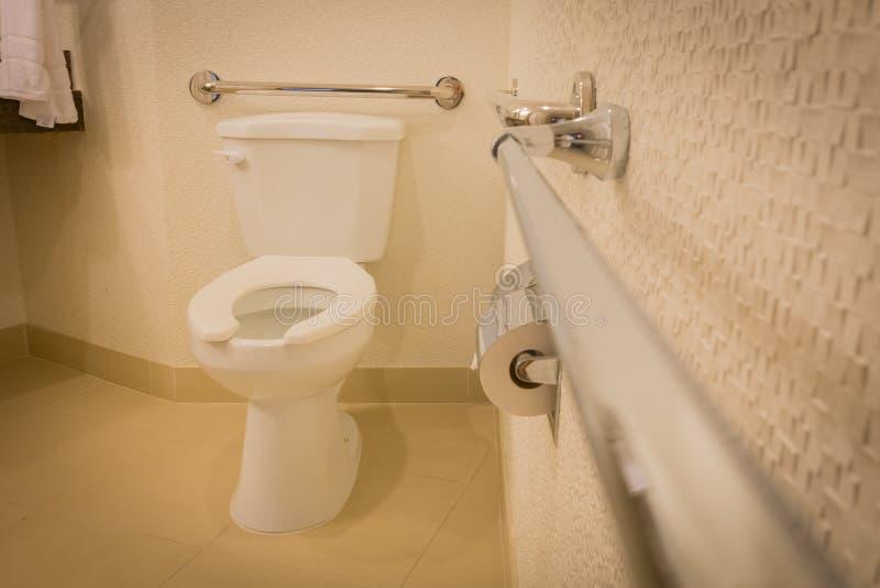 Bagno disabile della toilette con le barre di gru a benna nell'hotel bianco di interior design immagine stock libera da diritti