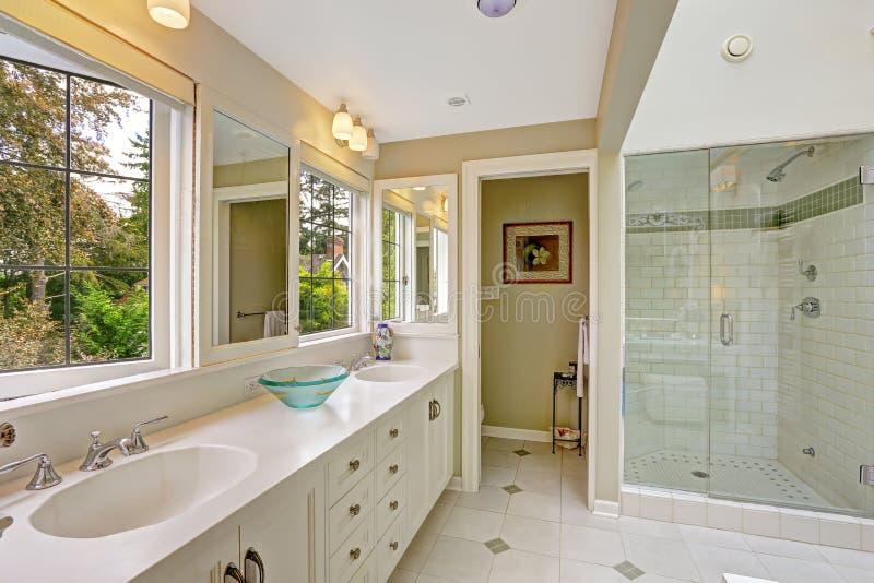 Bagno luminoso spazioso con la doccia di vetro della porta immagine stock libera da diritti