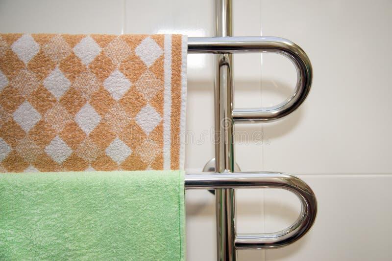 Bagno moderno con lo scaldino dell'asciugamano con l'asciugamano verde e marrone fotografia stock libera da diritti