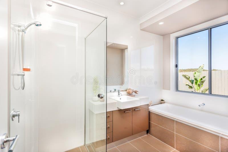 Bagno moderno con un rubinetto, vasca di acqua e piastrelle per pavimento marroni scure fotografia stock libera da diritti
