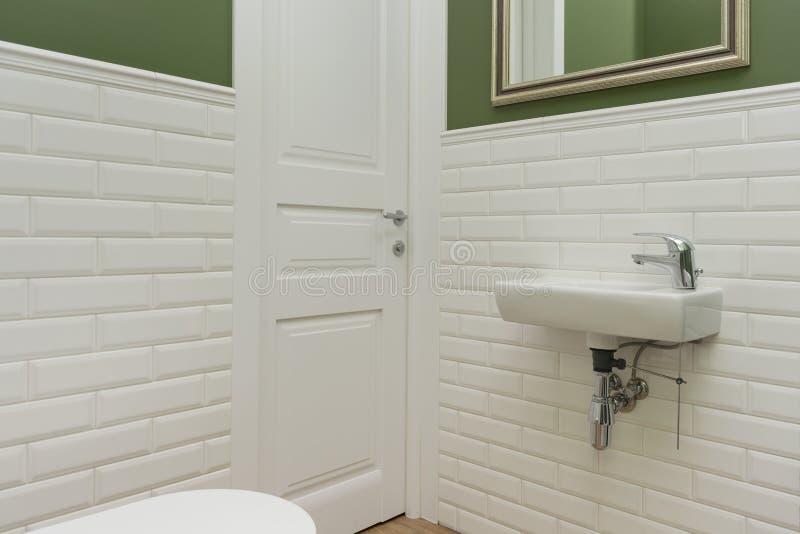 Bagno, primo piano dell'interno della stanza della toilette Le pareti sono dipinte verdi, coperto di piastrelle di ceramica decor fotografie stock