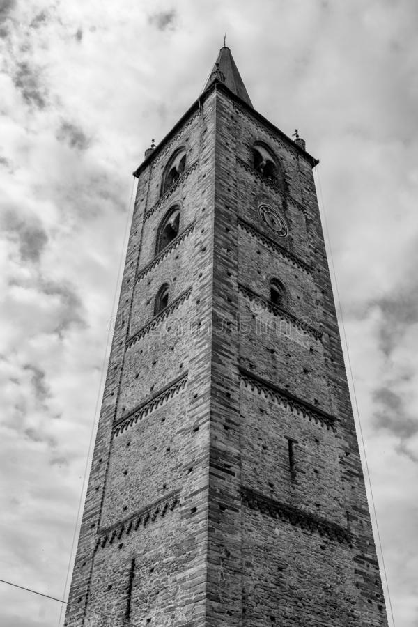 Bagnolo Piemonte, Cuneo, historic tower. Bagnolo Piemonte, Cuneo, Piedmont, Italy: medieval belfry of the San Pietro in Vincoli church. Black and white stock photography