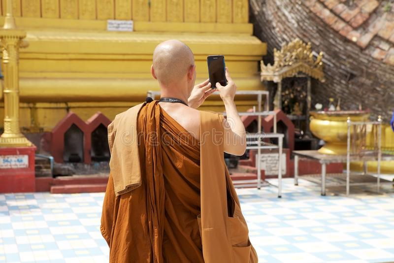 Bago. Buddhist monk in traditional robes is taking photo by cellular phone at the Shwemawdaw Paya, Bago, Myanmar. Shwemawdaw Paya is a stupa located in Bago royalty free stock images