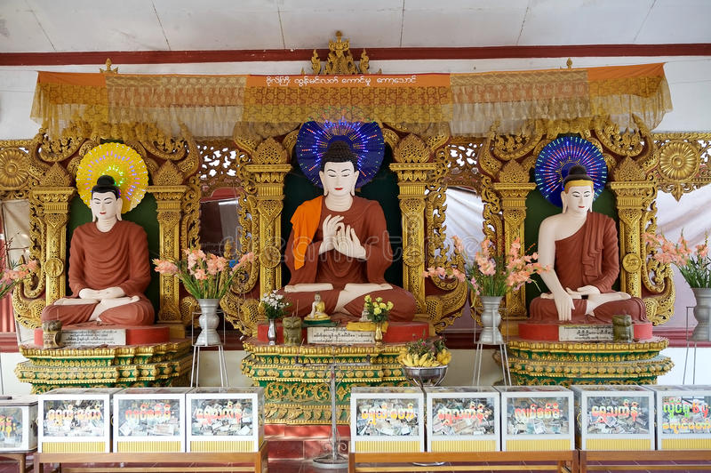 Bago. Three statues of Buddha at the temple near the entrance to Kyaik Pun pagoda, Bago, Myanmar, with the offering boxes full of money stock images