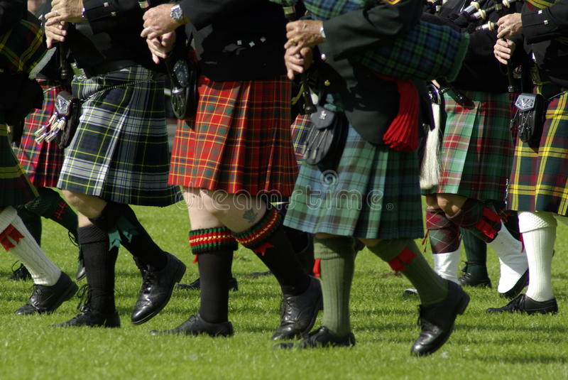 Bagpipe band. Bagpipe players walking on the grass, Edinburgh, the gathering royalty free stock photo