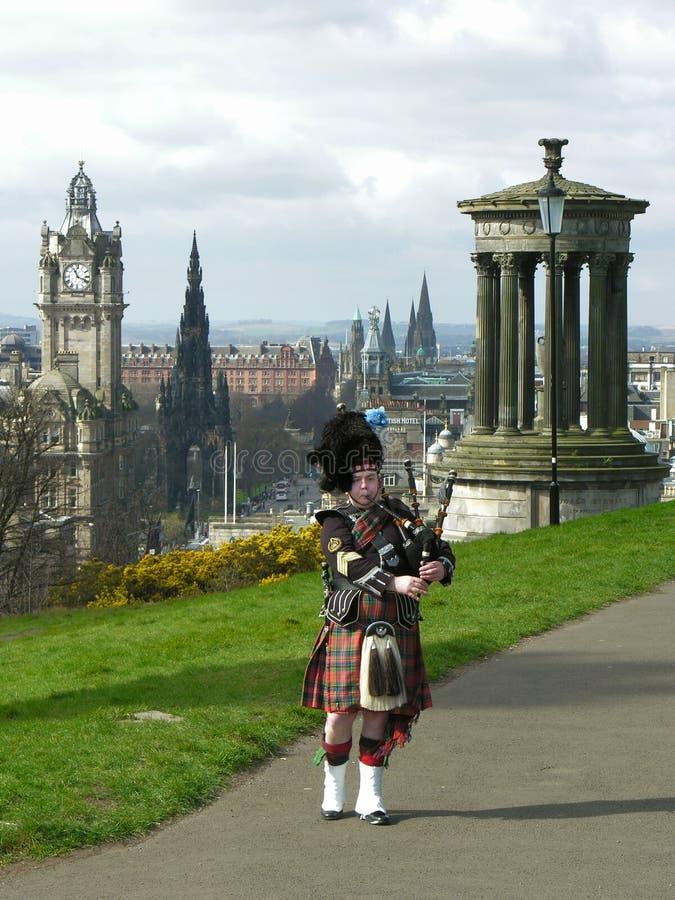 Bagpiper busker in Edinburgh, vertical cityscape royalty free stock photo