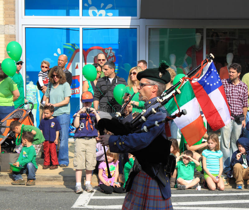 Bagpiper with Flags. Bagpipers with flags at St Patrick Days Parade royalty free stock image