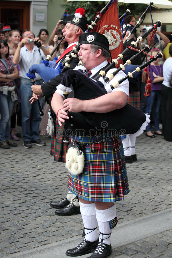Bagpiper in kilt playing Scotish bagpipe royalty free stock photo