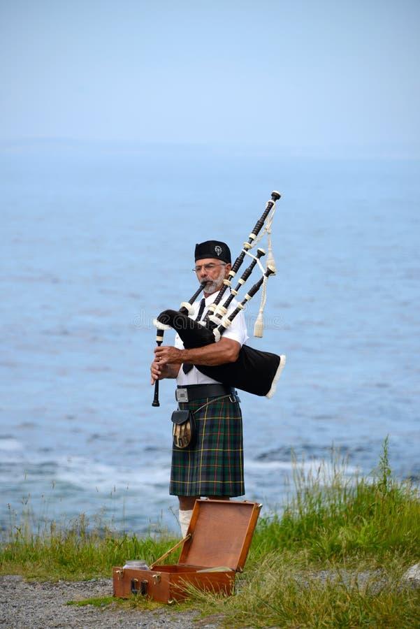 Bagpiper wearing kilt at the coast royalty free stock image