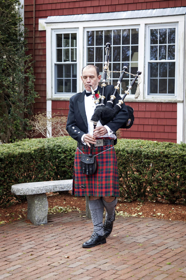 Bagpiper wearing kilt. Traditional bagpiper wearing plaid kilt and playing bagpipes