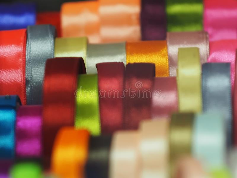 Bags bows ribbons like rainbow in the right hands. Satin ribbon silk different, colors shapes materials blue pink red blue beige background haberdashery backing royalty free stock photos