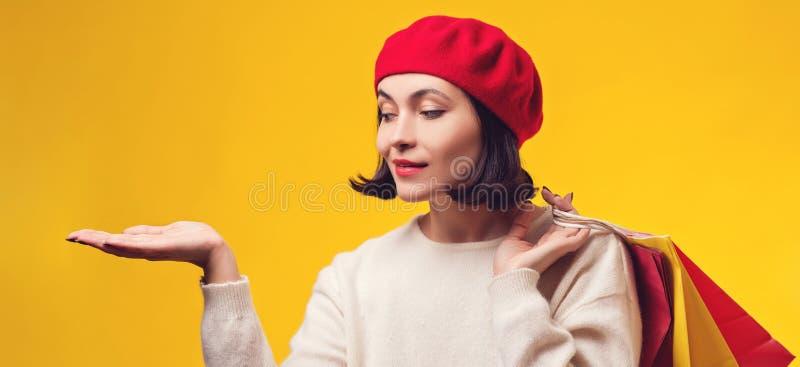 bags flickan som rymmer n?tt shopping Kvinna i röd hatt med presentation Flickan som visar din produkt med den öppna handen, gömm arkivbild