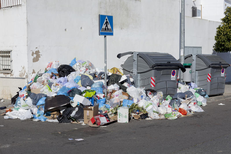Bags full of trash surrounding dumpsters, angle view royalty free stock images