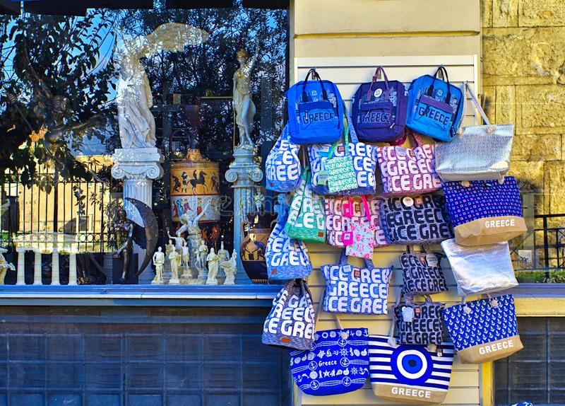 Bags with Greece printed on their sides hanging outside of souvenir shop royalty free stock photos