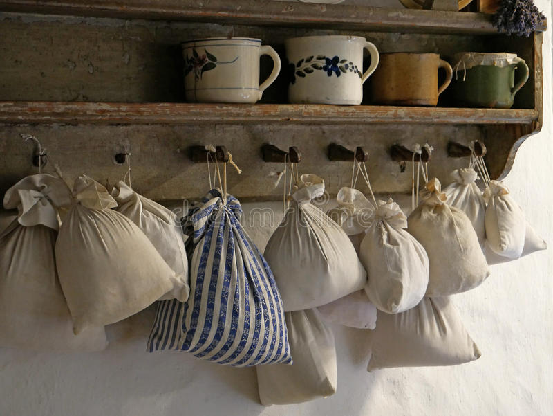 Bags of herbs. Pouches with fragrances. Clay mugs on a shelf stock photography