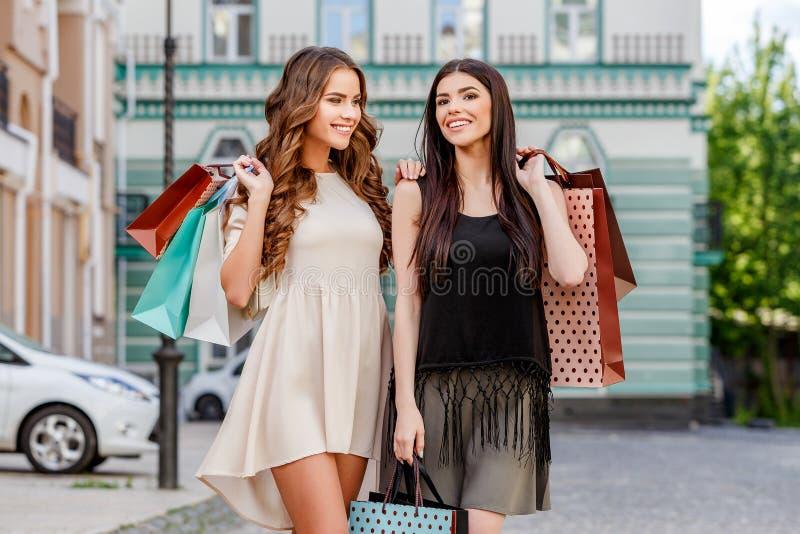 bags lyckliga unga shoppingkvinnor royaltyfria foton