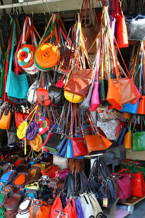 Bags at market stall. Rows of colorful leather purses and bags at market stall stock images