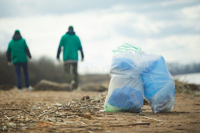 Bags and walking volunteers stock image