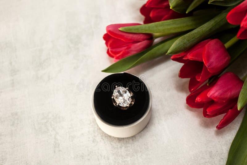 Bague de fiançailles haute étroite avec le diamant géant dans un boîtier blanc rond sur affiler le fond gris et avec un bouquet d photo libre de droits