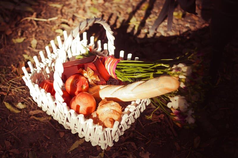 Baguette, appelen en bloemen in de witte mand royalty-vrije stock afbeeldingen