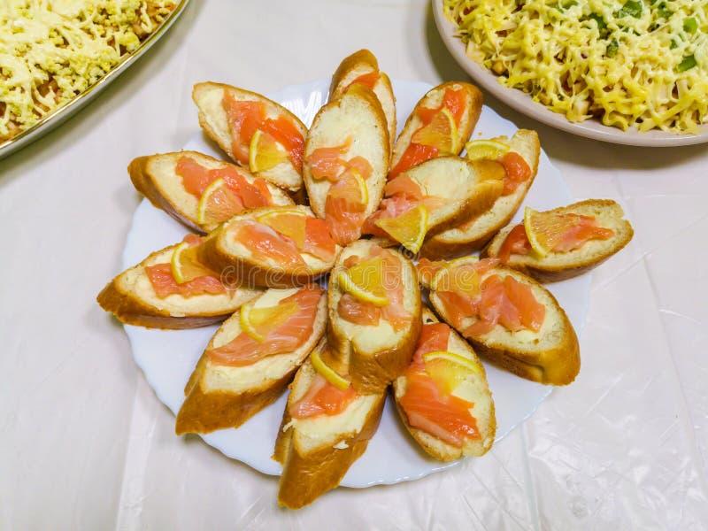 Baguette avec les poissons et le citron, tranches de saumons sur des tranches de citron photo libre de droits