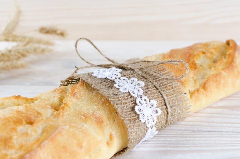 Baguette blanco fresco envuelto en arpillera imágenes de archivo libres de regalías