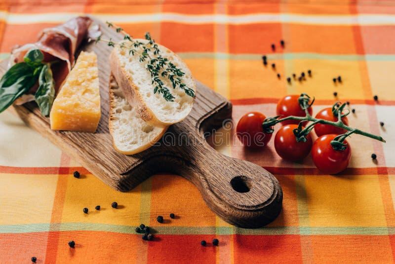 baguette, carne y queso parmesano cortados en tabla de cortar de madera y los tomates de cereza frescos fotos de archivo