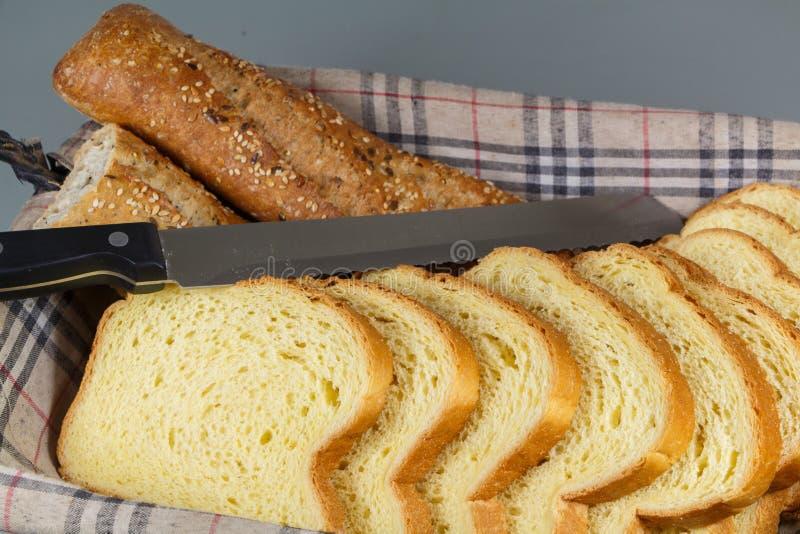 Baguette chleb, brioche i nóż w koszyku na chleb, zdjęcie stock