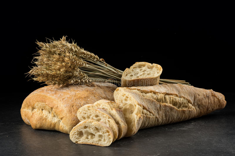 Baguette and ciabatta, bread slices on dark wooden table. Wheat and fresh mixed breads on black background. royalty free stock photos