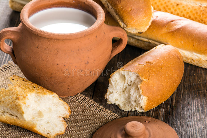 Baguette and clay pot with milk royalty free stock photography