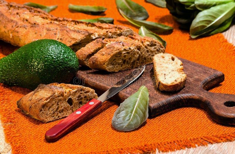 Baguette con l'avocado e la lattuga sulla lavagna della cucina fotografie stock