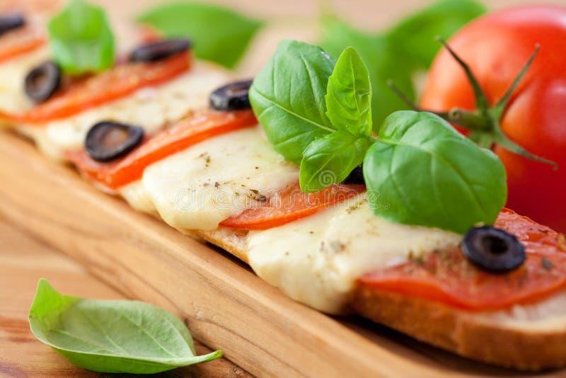 Baguette cotto con la mozzarella ed i pomodori immagini stock libere da diritti