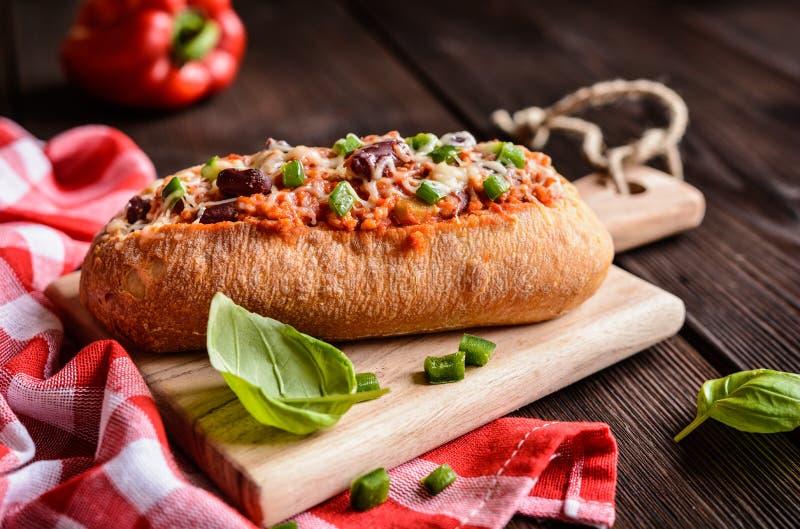 Baguette enchido com carne, molho de tomate, pimenta de sino, os feijões, a cebola, alho e queijo triturados fotografia de stock royalty free